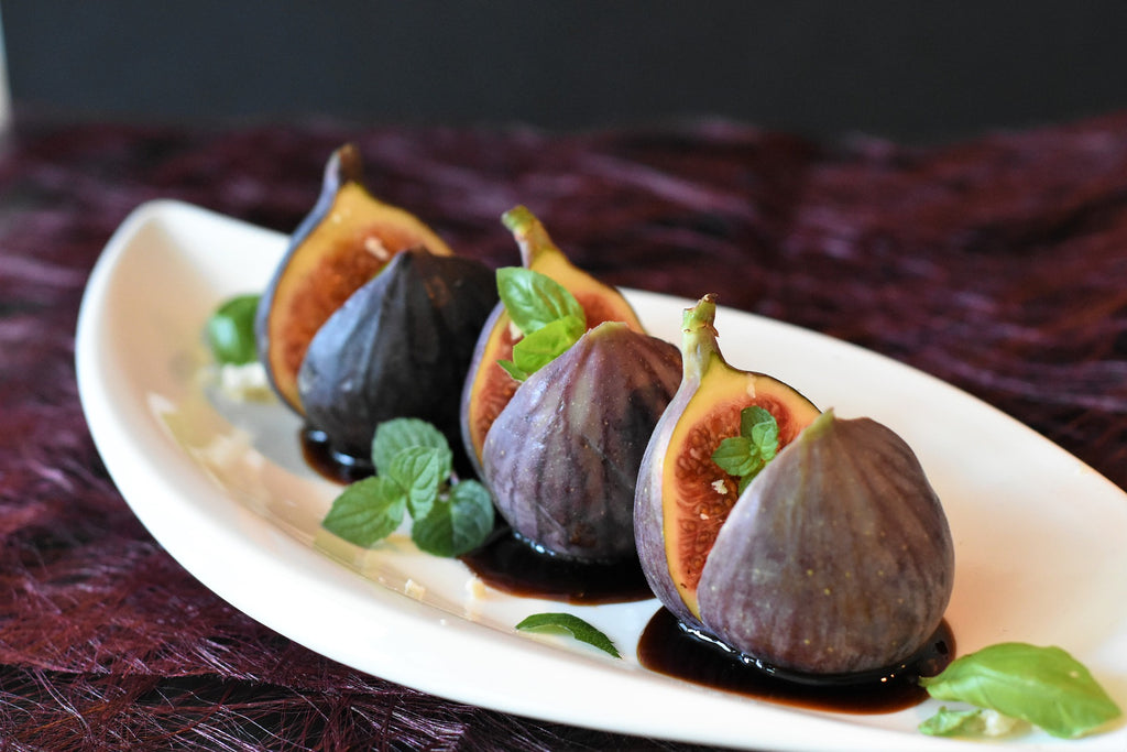 a plate of three figs with balsamic vinegar