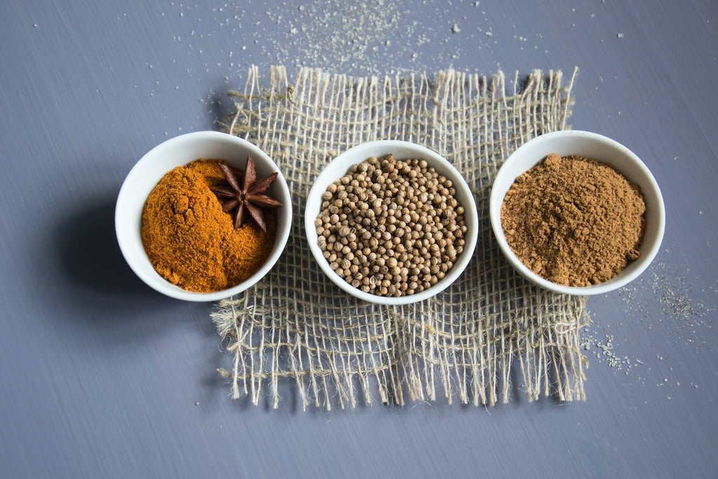 spices stored in small open white bowls