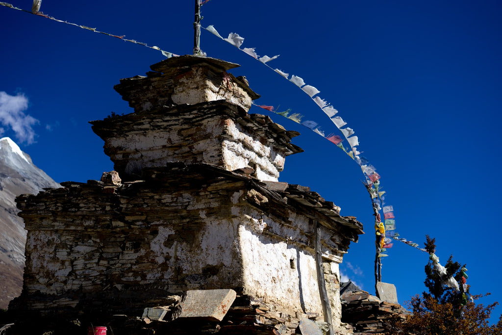 buddhist stupa and prayer flags in himalayan mountains