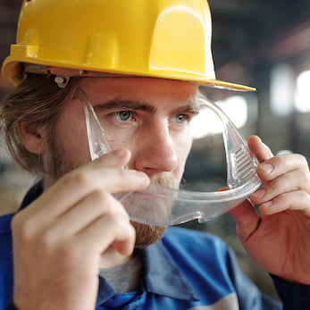 Man wearing hardhat putting safety goggles on