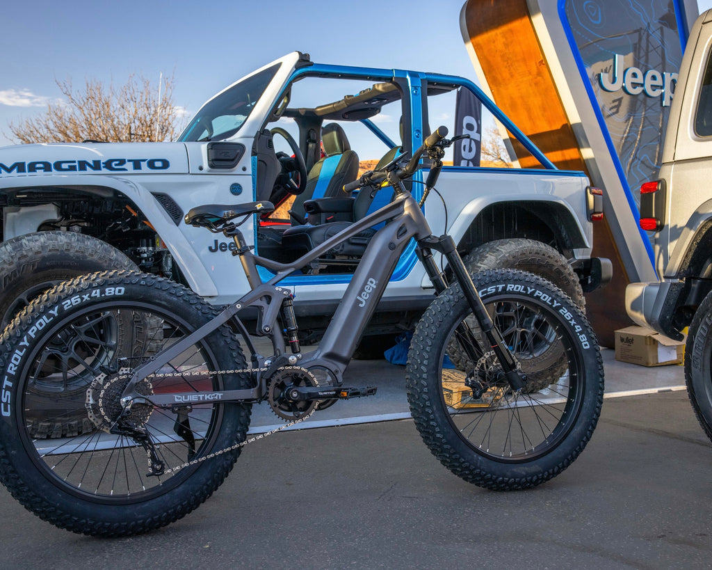 A QuietKat Jeep eBike is parked next to a white Jeep Wrangler