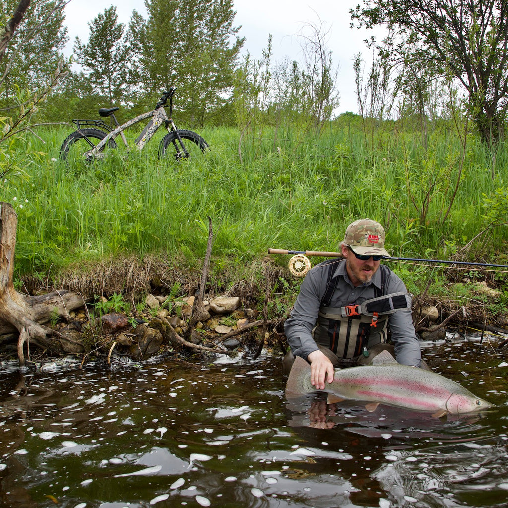 An angler releases a trout with his QuietKat electric fishing bike in the background