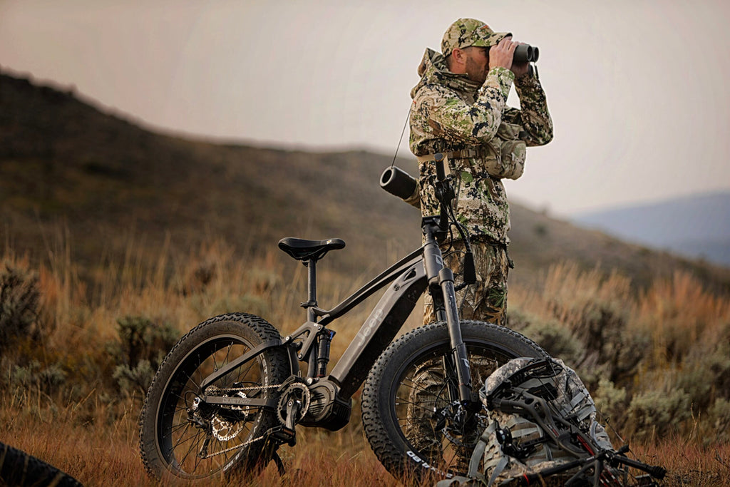 A hunter standing next to his QuietKat Jeep eclectic hunting bike looks for game through a pair of binoculars