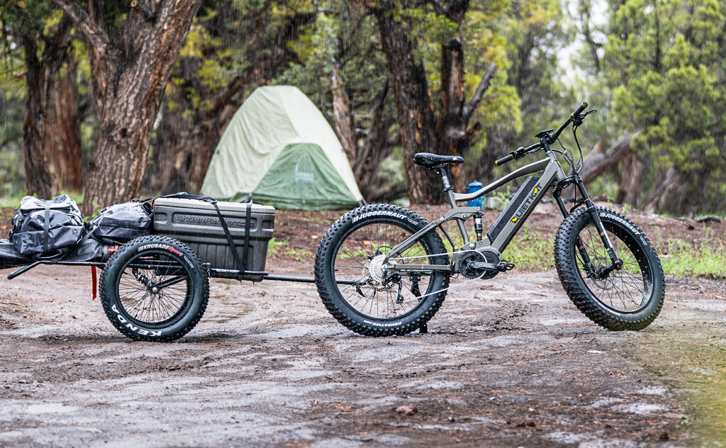 A QuietKat electric bike with a two wheel trailer is parked on a dirt trail with a tent in the background.