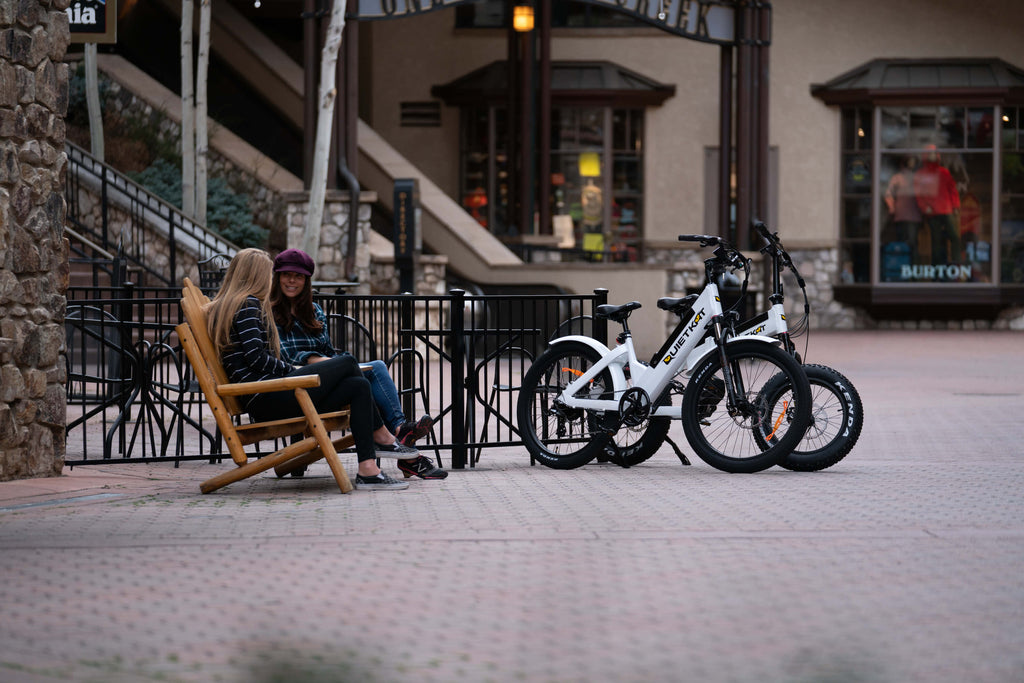 Two women sit on a bench by their parked QuietKat electric bikes near a cafe.