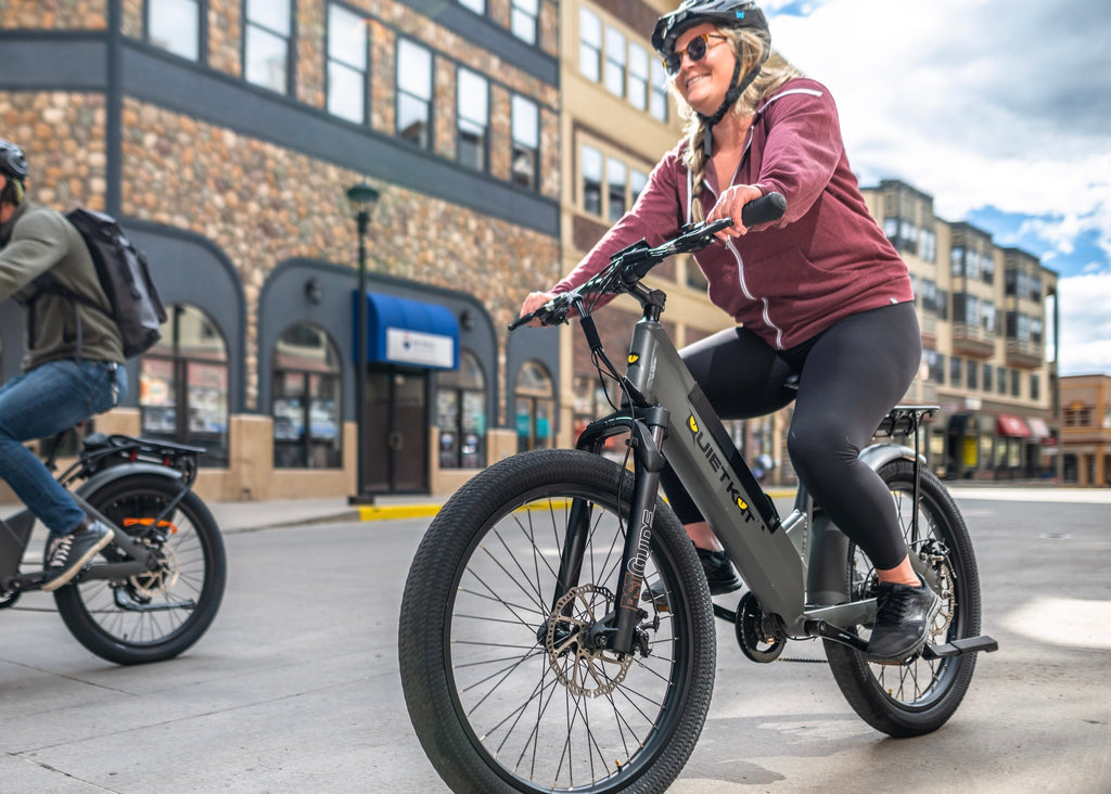 A woman practices electric bike safety by wearing her helmet while riding.