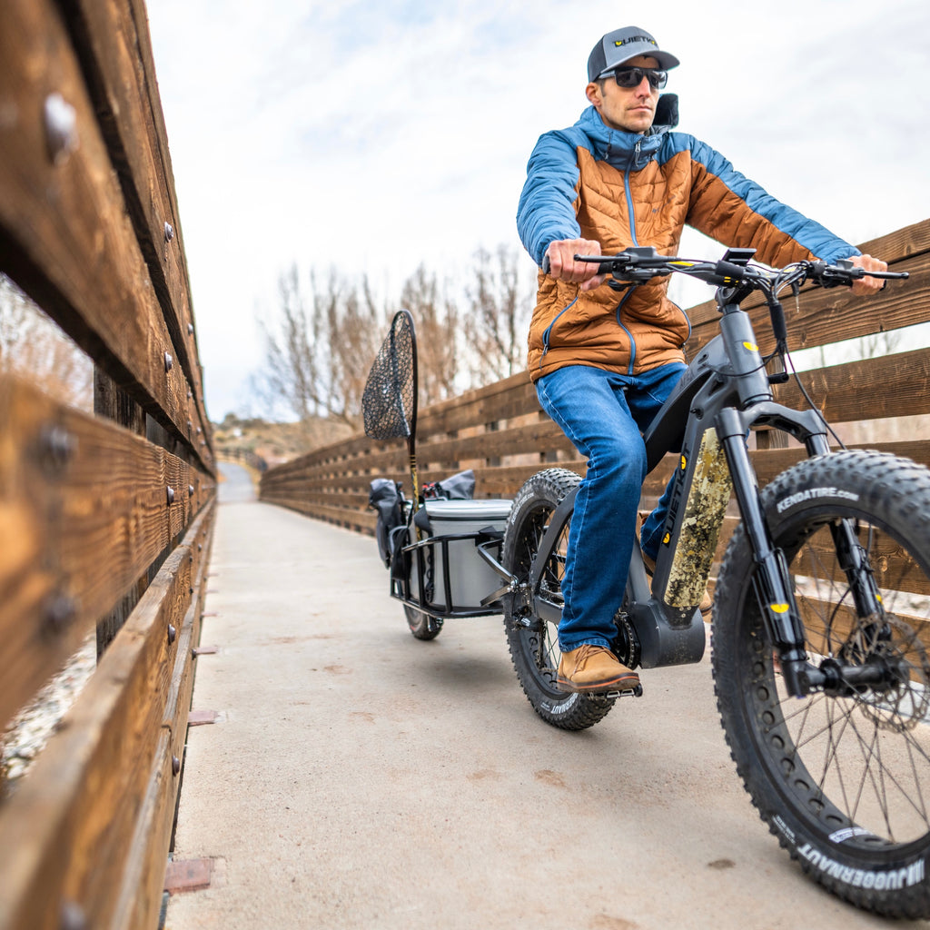 An angler rides his Quiet Kat fishing eBike towing a trailer of fishing gear