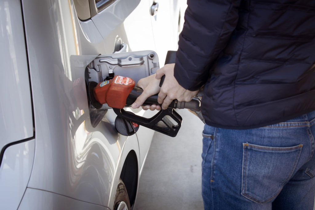 A person fills up their car at a gas station.