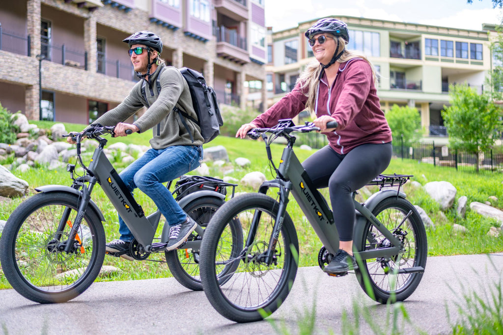 a man and a woman ride there QuietKat Villager eBike through town