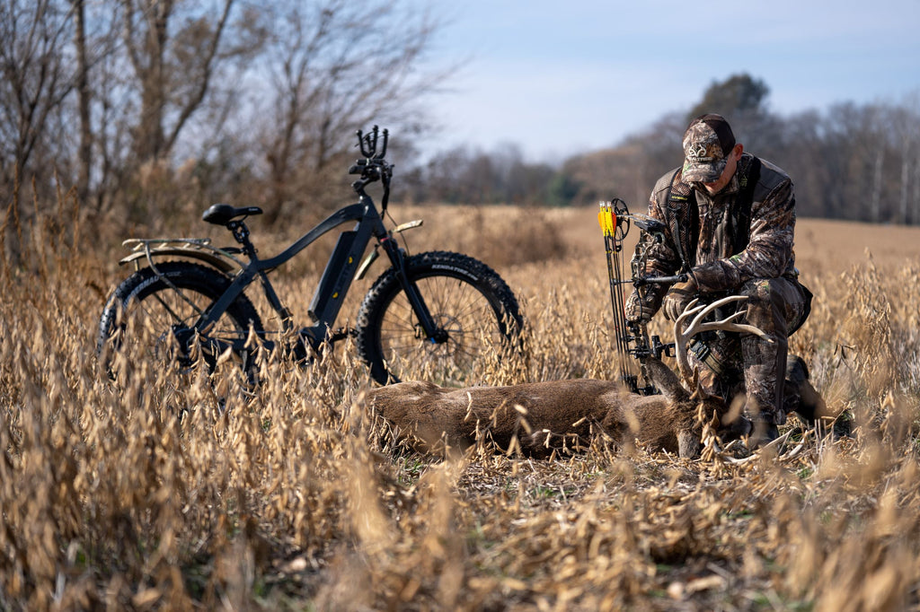 A bow hunter kneels besides a fallen buck with a QuietKat electric hunting bike in the background