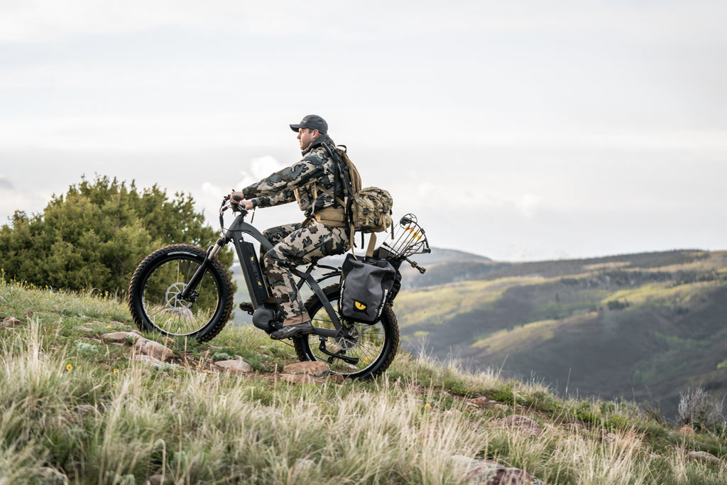 A hunter wearing camo climbs a steep hill on his QuietKat electric hunting bike