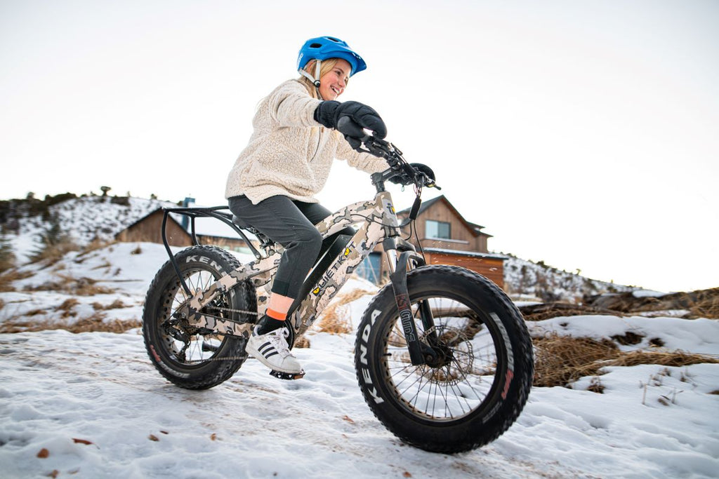 A girl rides her QuietKat Ripper eBike for kids down a snowy path