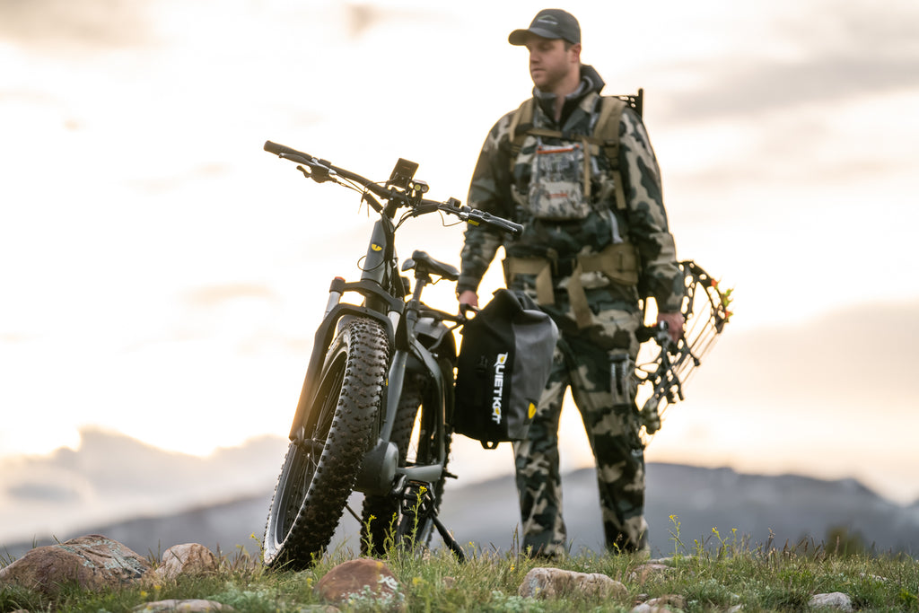 A bow hunter looks out ove rteh landscape while standing by his QuietKat electric bike with pannier bags.