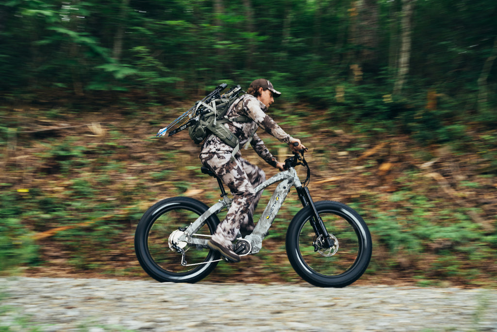 A turkey hunter in gray camo rides through the woods on his QuietKat hunting eBike