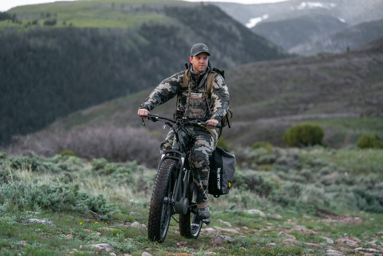 A hunter riding with an electric bike