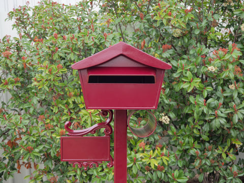 red kooyonga freestanding letterbox with bushes in background