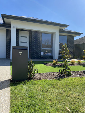 horizontal pillar letterbox in front of house