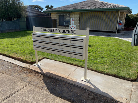 cream multibank bolted onto posts on concrete with signage plate