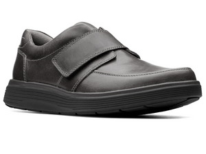 This black leather shoe has apron contrast stitching in the front, a large velcro strap that opens up the shoe to get in and out of easily.  As well it features a padded heel collar and black cushioned sole.