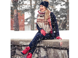 A women sitting on a stone wall with her red sound boots on in a winter wonderland.  Boots go great with jeans for a casual fun look.