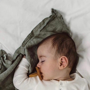 Sleeping baby with : Natural Rubber Eco Dummy, round/cherry teat, eco packaging, natural rubber colour.