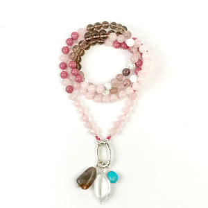 This mala necklace was created with beautiful 8mm Rose Quartz, Smoky Quartz, Strawberry Quartz, Rhodonite, and Howlite beads. This mala comes with a Crystal Quartz charm like the one pictured (other charms are for show only and can be purchased separately).