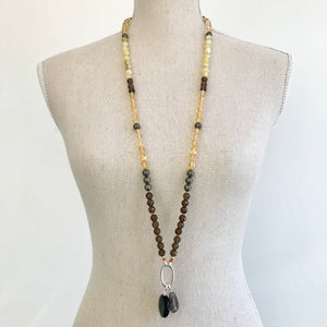 This mala necklace was created with beautiful 8mm Citrine, faceted Smoky Quartz, Yellow Opal, and Pyrite beads. It comes with a Crystal Quartz charm like the one pictured (other charms are for show only and can be purchased separately).