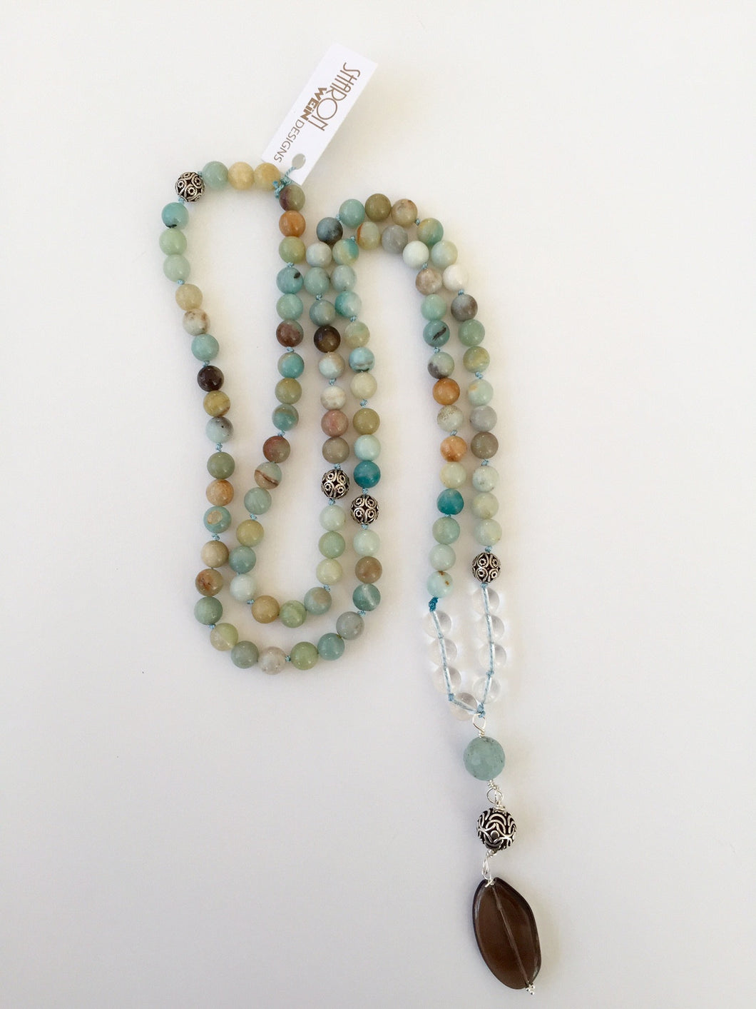 This Mala necklace is made of amazonite, smoky quartz, aquamarine, bali silver beads and silk. It measures 18.5