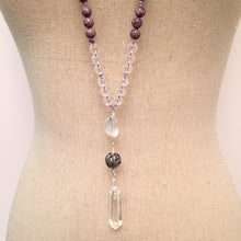 "Load image into Gallery viewer, This Mala necklace is made with lepidolite, crystal quartz, a bali bead and a crystal quartz point.  Lepidolite is the perfect stone to take you forward into the future. It's a very useful stone in the reduction of stress.  It helps you stand in your own space encouraging independence and achieving goals on your own. It's a calming and soothing stone.  This Mala is lovingly knotted every three beads with natural silk. It measures 18"" long without the guru bead. The stones are 8 mm."