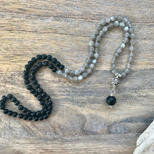 Load image into Gallery viewer, This mala necklace features 6mm Grey Moonstone and and Black Obsidian beads. The guru is handwired with .925 Sterling Silver and features a Sterling Silver carved Bali bead followed by a round matte Black Obsidian bead.