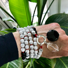 Load image into Gallery viewer, This mala necklace was created with beautiful 8mm matte Black Obsidian and faceted Howlite beads. It comes with a Crystal Quartz charm like the one pictured (other charms are for show only and can be purchased separately).