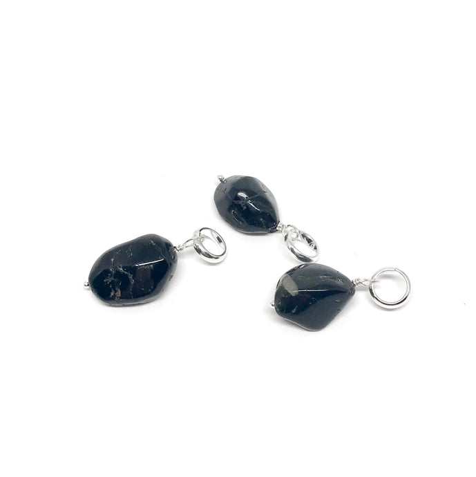 These tumbled Black Tourmaline gemstones have been carefully wire wrapped with Sterling Silver and attached to a closed 7mm Sterling Silver jump ring. They will fit most necklaces and most clasps.