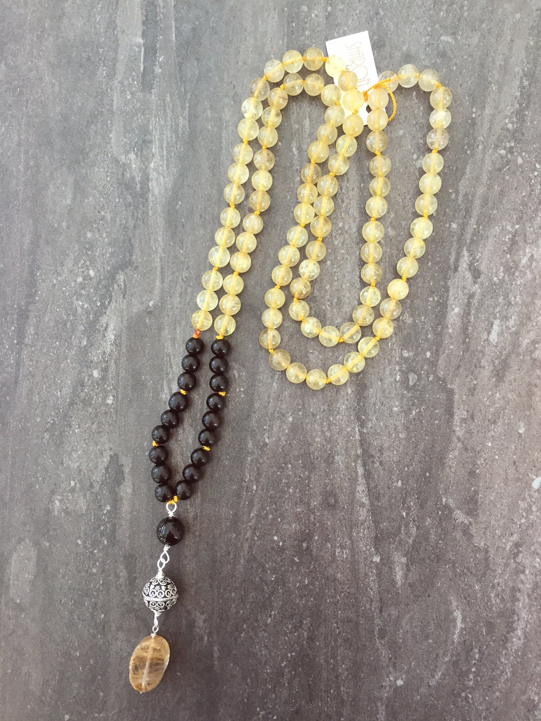 This Mala necklace is made of golden rutilated quartz, ebony wood, onyx,sterling silver and silk. It measures 18.5