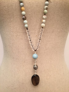 "This Mala necklace is made of amazonite, crystal quartz, smoky quartz and a bali silver bead. Amazonite will remind you to be trusting in yourself and to be brave. It's also a very soothing stone that will bring you comfort.  This Mala is lovingly knotted every three beads with natural silk. It measures 18"" long without the guru bead. The stones are 8 mm."