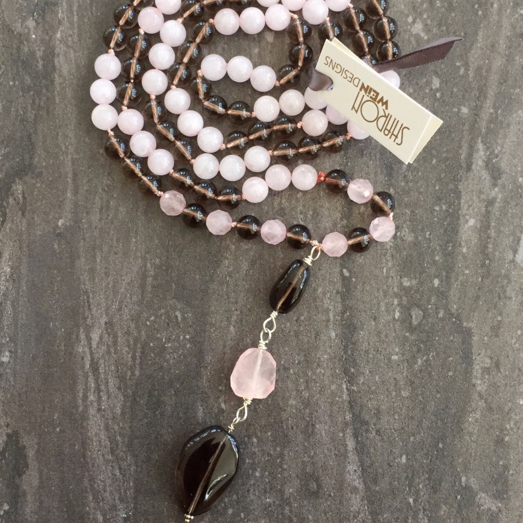 This Mala necklace is made of pink quartz, smoky quartz, sterling silver and silk. It measures 18.5