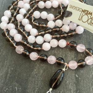 "This Mala necklace is made of pink quartz, smoky quartz, sterling silver and silk. It measures 18.5"" plus the guru bead."