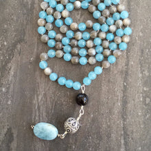 "Load image into Gallery viewer, This Mala necklace is made of grey moonstone, blue agate, onyx, a bali bead and aquamarine. This Mala is lovingly knotted every three beads with natural silk. It measures aprox. 18"" long without the guru bead. The stones are 6mm."