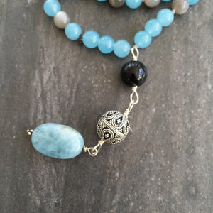 "This Mala necklace is made of grey moonstone, blue agate, onyx, a bali bead and aquamarine. This Mala is lovingly knotted every three beads with natural silk. It measures aprox. 18"" long without the guru bead. The stones are 6mm."