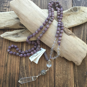 "This Mala necklace is made with lepidolite, crystal quartz, a bali bead and a crystal quartz point.  Lepidolite is the perfect stone to take you forward into the future. It's a very useful stone in the reduction of stress.  It helps you stand in your own space encouraging independence and achieving goals on your own. It's a calming and soothing stone.  This Mala is lovingly knotted every three beads with natural silk. It measures 18"" long without the guru bead. The stones are 8 mm."