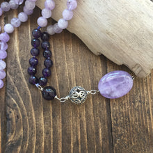 Load image into Gallery viewer, This mala is made with beautiful 8mm dark purple and lavender amethysts beads. The guru is made with a large round amethyst bead, sterling silver Bali bead and a smooth oval large lavender amethyst bead. Amethyst is a powerful and protective stone and a natural tranquilizer. It will help you to remain calm and focused making you more able to set realistic goals.