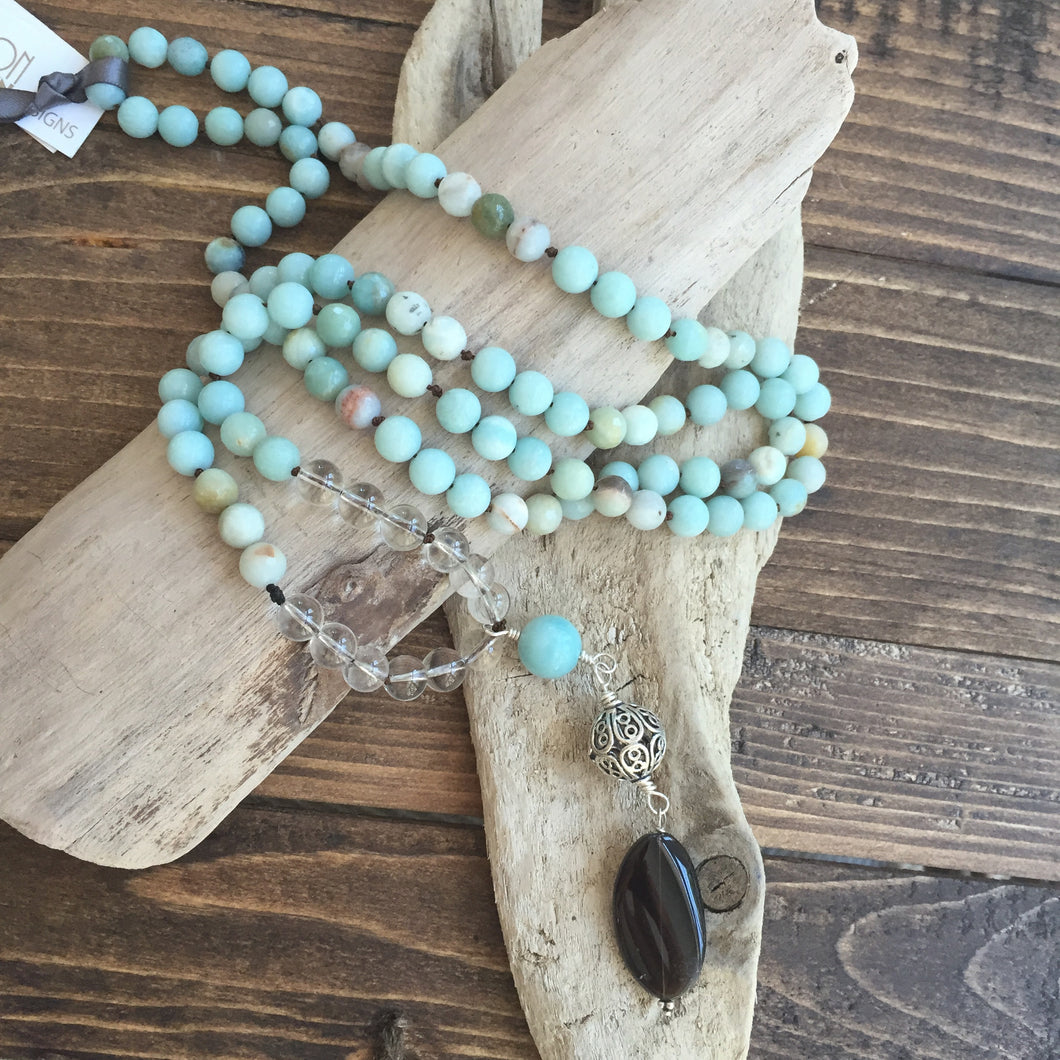 This Mala necklace is made of amazonite, crystal quartz, smoky quartz and a bali silver bead. Amazonite will remind you to be trusting in yourself and to be brave. It's also a very soothing stone that will bring you comfort.  This Mala is lovingly knotted every three beads with natural silk. It measures 18