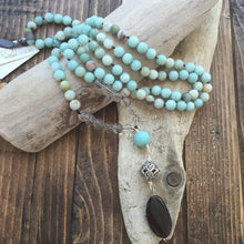 "Load image into Gallery viewer, This Mala necklace is made of amazonite, crystal quartz, smoky quartz and a bali silver bead. Amazonite will remind you to be trusting in yourself and to be brave. It's also a very soothing stone that will bring you comfort.  This Mala is lovingly knotted every three beads with natural silk. It measures 18"" long without the guru bead. The stones are 8 mm."