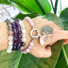 Load image into Gallery viewer, This mala necklace was created with beautiful 8mm Kunzite, Charoite, Amethyst and Moonstone beads. It comes with a Crystal Quartz charm like the one pictured (other charms are for show only and can be purchased separately).