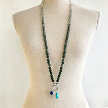 Load image into Gallery viewer, This mala necklace was created with beautiful 8mm Onyx, Snowflake Obsidian, Black-Grey Rutilated Quartz, Hematite, Howlite, Larvikite, and Moonstone beads. It comes with a Crystal Quartz charm like the one pictured (other charms are for show only and can be purchased separately).
