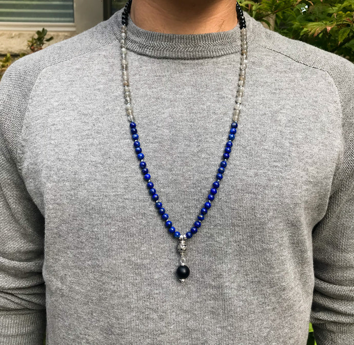 This mala necklace features 6mm lapis lazuli, grey moonstone and blue tiger eye beads. The guru bead is made with a sterling silver carved Bali bead followed by a round matte black obsidian bead, all hand wired with .925 Sterling Silver.
