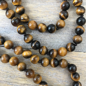 This Mala necklace features tiger eye and crystal quartz gemstones and the Guru is made with a large tiger eye bead followed by a large black lava bead all hand wired with .925 Sterling Silver.