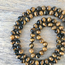 Load image into Gallery viewer, This Mala necklace features tiger eye and crystal quartz gemstones and the Guru is made with a large tiger eye bead followed by a large black lava bead all hand wired with .925 Sterling Silver.