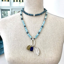Load image into Gallery viewer, This mala necklace was created with beautiful 8mm matte and polished Aquamarine beads in different hues. It comes with a Crystal Quartz charm like the one pictured (other charms are for show only and can be purchased separately).