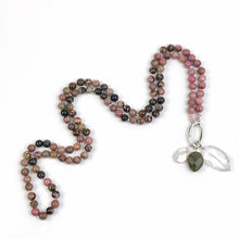 "Load image into Gallery viewer, This mala necklace was created with beautiful 8mm Rhodonite gemstone beads.  It comes with a Crystal Quartz charm like the one pictured (other charms are for show only and can be purchased separately).  Number of semi precious beads: 108 Size of beads: 8mm Full hanging length: 19"" approx."