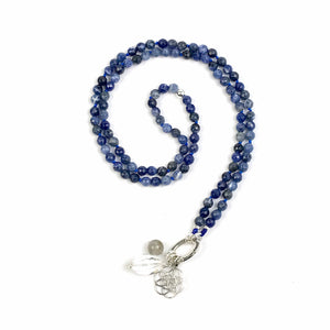 This mala necklace was created with beautiful 6mm Soldalite beads with a Sterling Silver bead at the midpoint. It comes with a Crystal Quartz charm like the one pictured (other charms are for show only and can be purchased separately).